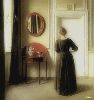 Interiør med dame set fra ryggen. 1901